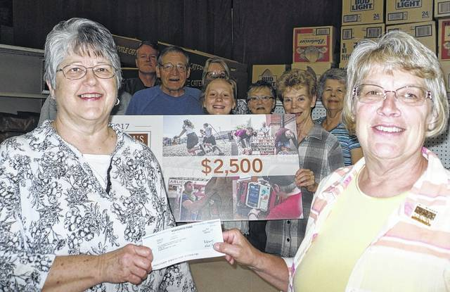 Volunteers at the United Christian Churches Food Pantry were all smiles when the Monsanto Fund presented a $2,500 donation to Pantry President Sue Hurley, left. Local farmer Rozanna Shoffstall, right, nominated the pantry to receive the donation.