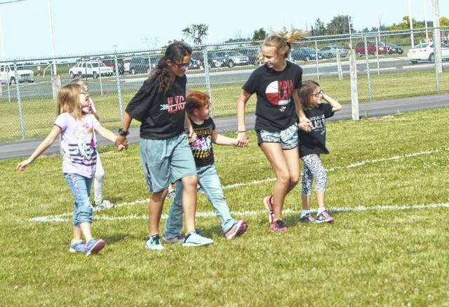 ILMS Cross Country runner Rachel Wahl and ILHS Cross Country runner Ella Wagner help Little Lakers Running Club members complete their race at the end of practice.