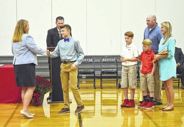 Indian Lake Middle School Co-Principal Missy Mefford presents Nate Cummins with his award for being inducted into the ILMS Academic Hall of Fame while his parents and brothers watch.