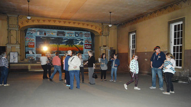 Tourists examine old advertising signs at the Opera House during the Oct. 21 event.