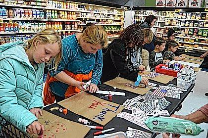 Indian Lake Elementary students decorate grocery bags to be given to veterans during the school's Family Fun Night at Community Markets in Lakeview.
