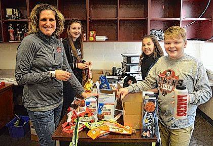 From left, Indian Lake Middle School Guidance Counselor Mandy Tidwell and 7th grade Student Council representatives Allison Kinney, Reece Martin and Colby Borgerding stuff boxes that will be mailed to Indian Lake graduates serving in the military.
