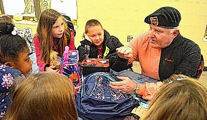 Army Special Forces veteran Donald T. Willis talks with students Brooklyn Evans, left, and Tristan Taylor, center, during the Veterans Day event at Indian Lake Elementary School.