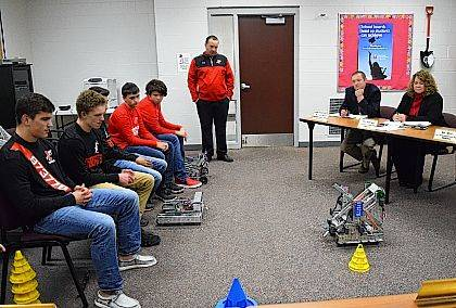 Members of Indian Lake High School Robotics Teams demonstrate tasks their robots must complete during VEX competitions while Robotics educator and club instructor Ryan Stanford explains the program to board members.
