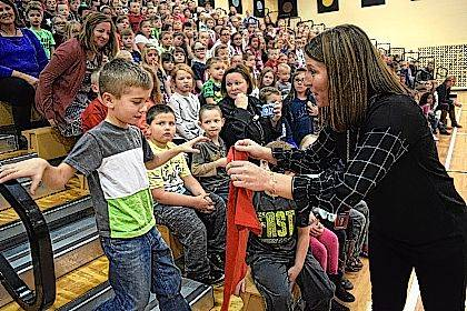 Indian Lake Elementary Co-Principal Molly Hall presents kindergartner Hayden Kuhlke with a Laker Zone T-shirt.