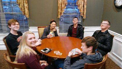 """The Indian Lake Youth Leadership Impact team organized a Game Night at the Homestead. Students from all of the schools' Impact teams were invited. Cole and Lane Mefford played euchre with the two local experts and Chase Coburn stayed close to learn the game. Others played Uno, Old Maid and the game of """"Life"""". Games were not the only activity. By request of the residents a table and chairs was designated for just chatting. Students sat around the table and visited and learned many things about each other."""