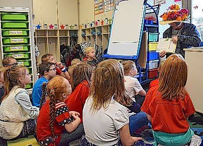 "Brenda Moots of Indian Lake Outfitters and The Depot in Lakeview wears a flowered hat as she reads her favorite children's book, ""Go Dogs, Go!"" to Mrs. Downing's first grade class."