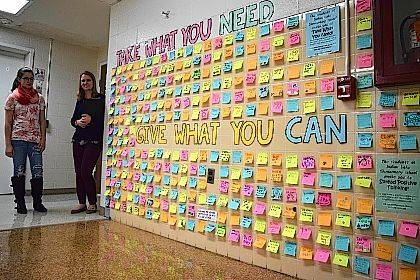 """Sophomore Danae Brown and math teacher Amber Shively stand by the """"Take What You Need, Give When You Can"""" wall at Indian Lake High School."""