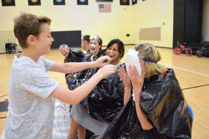 4th grader Brody Lewis shoves a pie in the face of 4th grade teacher Christi Warnecke.