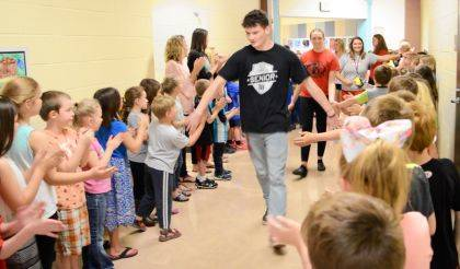 Indian Lake senior Charles Henderson-Wildermuth gives high-fives on both sides of the aisle at Indian Lake Elementary as he makes his way through the 2018 Senior Salute Clap Out.