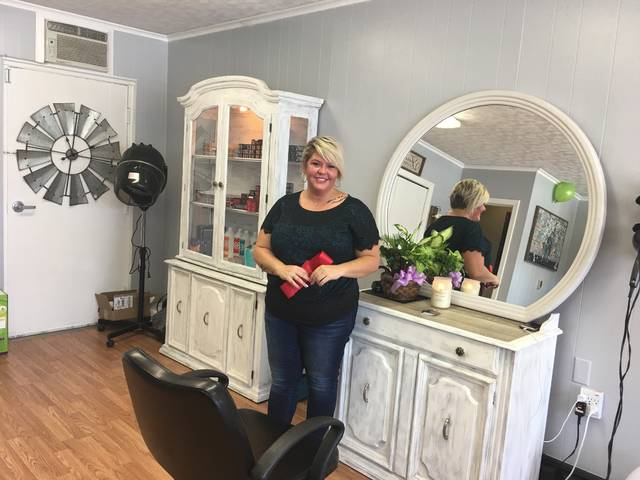 With Grand Opening ribbon in hand, happy proprietor Stephanie Inskeep proudly displays her new hair salon and Indian Lake's newest business.