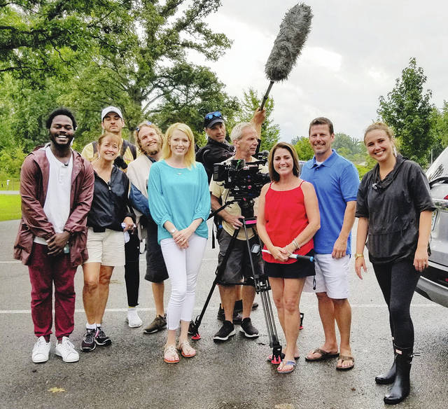 """Local Realtor Paige Duff, left of camera, poses with the production crew from Left Right LLC of New York City and two of the the local home buyers to be featured on the show. They just wrapped up shooting two episodes to air this year on HGTV's """"Island Life"""" reality show."""