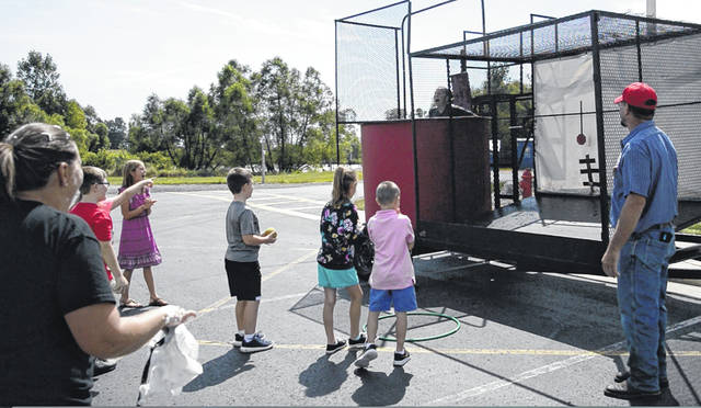Indian Lake Elementary Co-Principal Molly Hall falls into the dunk tank at the Summer Reading Celebration. Students who completed the log got a chance to dunk each principal.