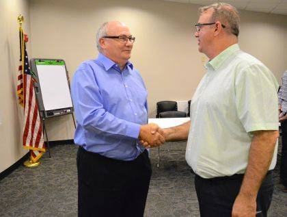 Fred Brentlinger, the city of Bellefontaine's new auditor, shakes hands with Jack Reser, former city auditor and new Logan County auditor, on Aug. 8.