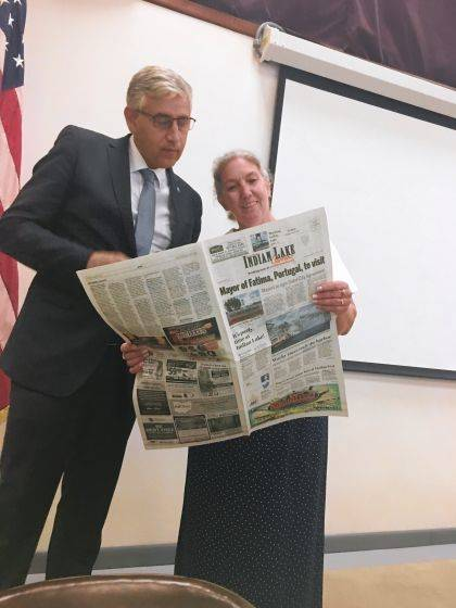Mayors Lu&#237;s Miquel Albuquerque and Robin Reames read an article in the <em>Indian Lake Current</em> about plans to sign a Sister City Agreement.