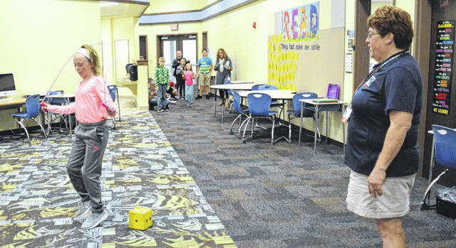 """Deb Orr leads 4th grader Jenna Cline in """"roll the dice jump rope"""" during Power Up 4 Fitness at Indian Lake Elementary School."""